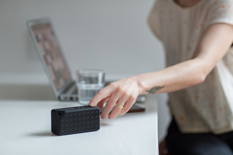 Woman Reaching for Black Bluetooth Speaker on Top of White Table