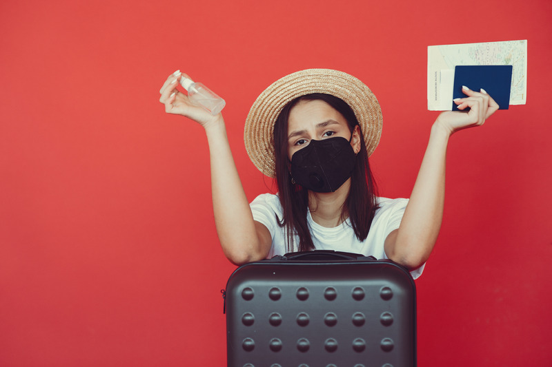 Young lady in mask with sanitize spray on red background